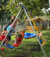 Children enjoying the swings in the backyard at The Green Preschool in Kailua.
